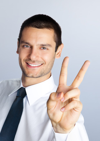 2 persons only: Cheerful smiling young businessman showing two fingers, or victory gesture, against grey background Stock Photo