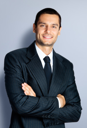 Portrait of cheerful young businessman with crossed arms pose, against grey background photo