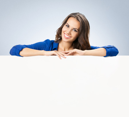 advertising space: Portrait of cheerful beautiful woman showing blank signboard with copyspace area for text or slogan
