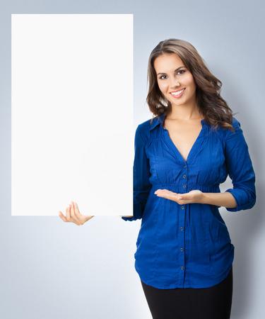 slogan: Retrato de mujer hermosa alegre que muestra el letrero en blanco con área de copyspace de texto o lema
