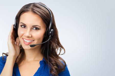 superficie: Retrato de la sonrisa hermosa joven operador de soporte telef�nico en el auricular, con zona de copyspace Foto de archivo