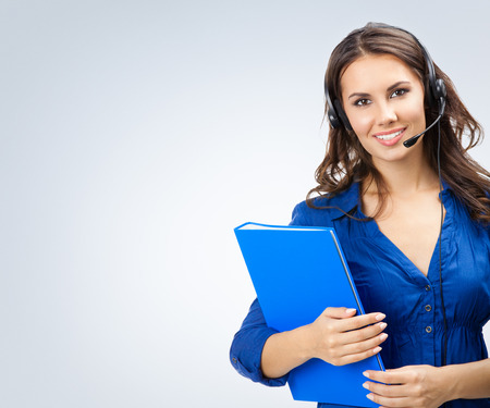 Portrait of cheerful beautiful young support phone operator in headset with blue folder, with copyspace area