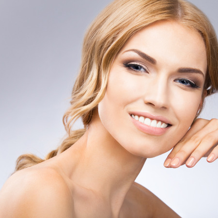 touching face: Portrait of beautiful young woman touching skin or applying cream, over grey background Stock Photo