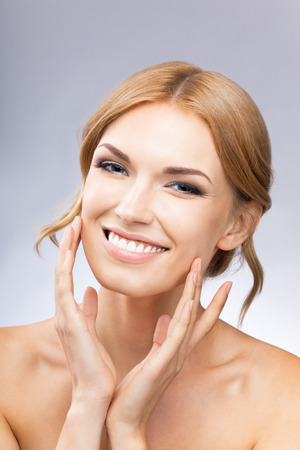 woman face cream: Portrait of beautiful young woman touching skin or applying cream, over grey background Stock Photo