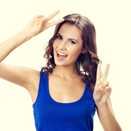 twenty two: Portrait of smiling young beautiful woman showing two fingers or victory gesture