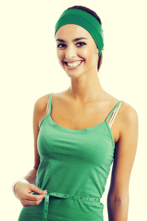 woman measuring waist: Cheerful young woman in green fitness wear measuring waist with a tape measure