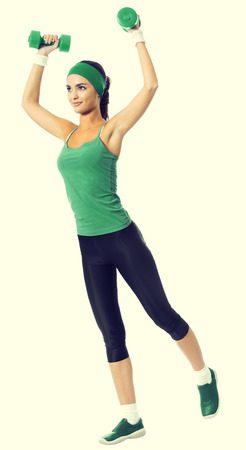 Full body of cherful young woman in green fitness wear exercising with dumbbells