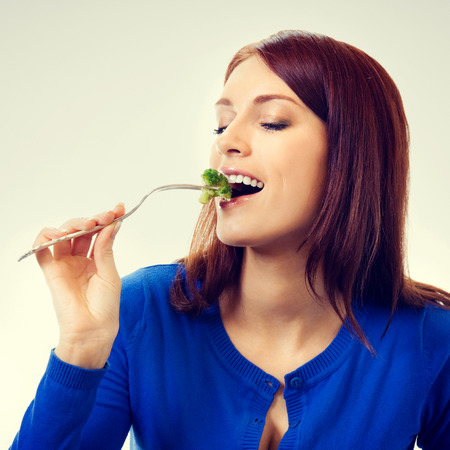 potherbs: Portrait of young beautiful woman eating broccoli