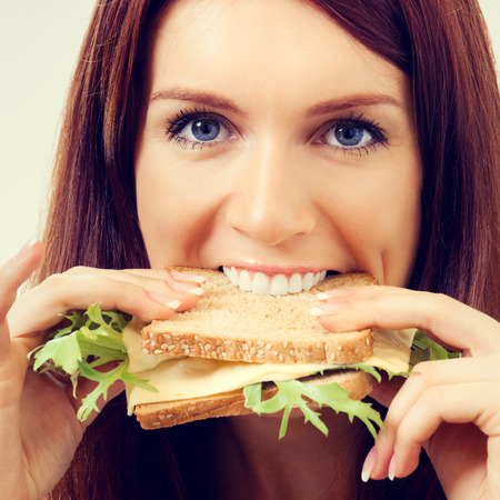 gluttonous: Portrait of young beautiful woman eating sandwich with cheese