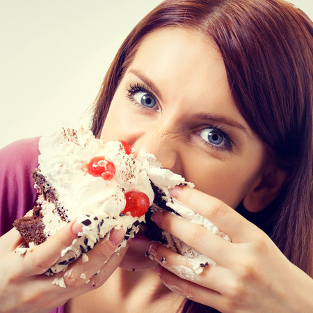 woman eating cake: Portrait of young hungry woman eating pie