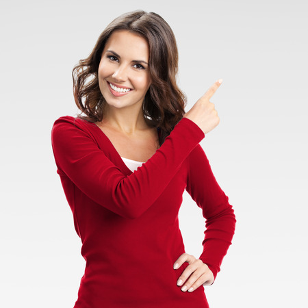 Porträt von fröhlichen jungen Frau zeigt copyspace, visuell imaginären oder etwas, oder drücken Sie virual Button, über grauem Hintergrund