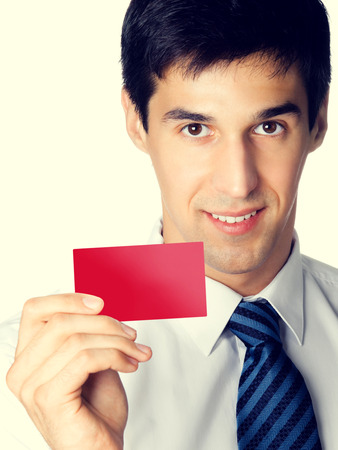 debet: Portrait of happy smiling young businessman giving blank red business or plastic credit card with copyspace area for text or slogan Stock Photo