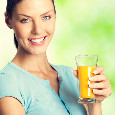 Portrait of cheerful smiling woman with glass of orange juice, outdoors photo