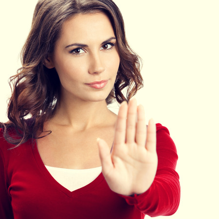 woman stop: Portrait of serious young woman showing stop gesture Stock Photo