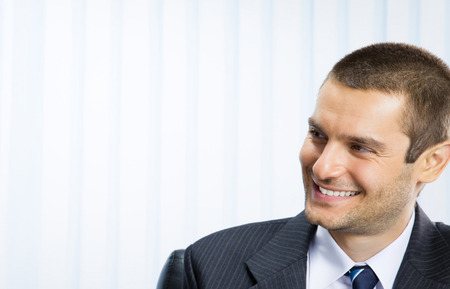young executives: Portrait of young cheerful businessman at office, with copyspace area for slogan or text