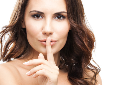 hearsay: Portrait of young woman with finger on lips, isolated against white background Stock Photo