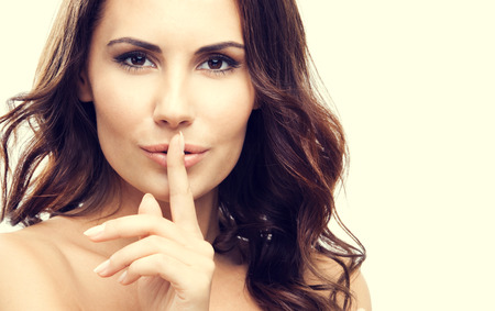Portrait of young woman with finger on lips, or secret gesture hand sign
