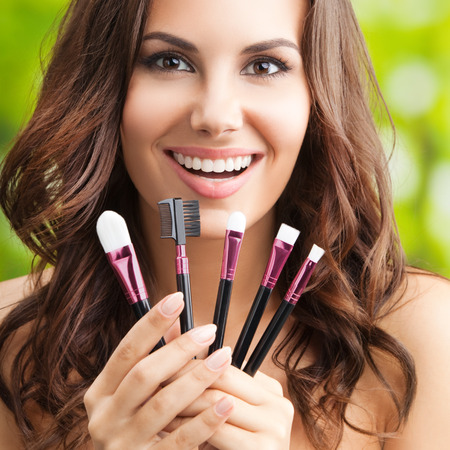 Cheerful smiling woman with make up tools, outdoor Stock Photo
