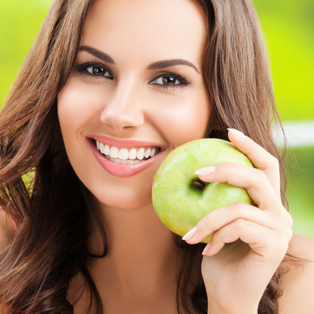 only one person: Cheerful smiling young woman with green apple, outdoor Stock Photo