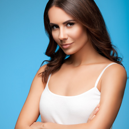 Portrait of happy smiling young beautiful woman in white casual clothing, over blue background photo