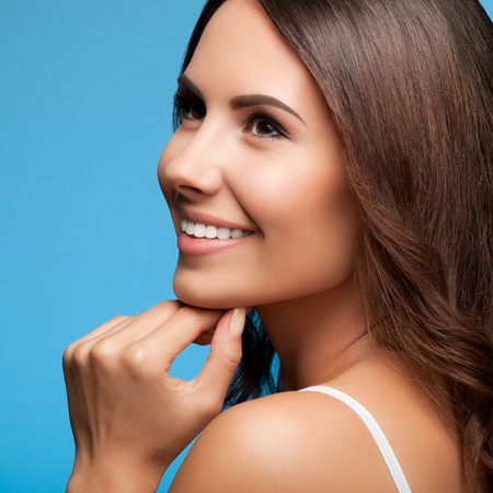 Portrait of thinking happy smiling young beautiful woman looking up, in white casual clothing, over blue background photo