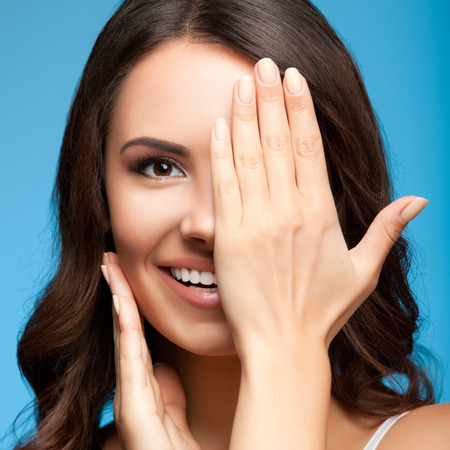 Concept photo of happy smiling young woman with one eye, closed by hand, covering part of her face, over blue background Stock Photo