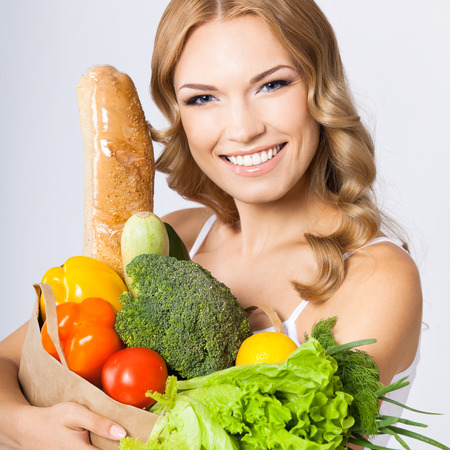 over eating: Portrait of happy smiling cheerful woman holding grocery shopping bag with healthy vegetarian raw food, against grey background. Healthy eating and dieting concept.