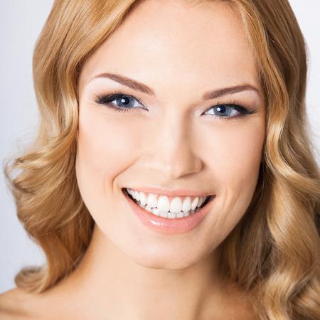 灰色背景: 若い陽気な幸せな笑顔の女性、灰色背景の肖像画 写真素材