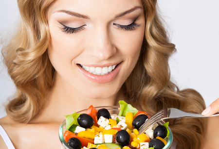 Portrait of cheerful smiling young blond woman eating vegetarian salad, against grey background. Healthy eating and dieting concept. photo