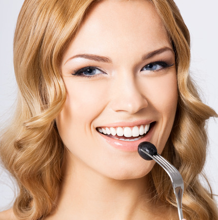 Portrait of cheerful smiling young blond woman eating black olive, against grey background photo