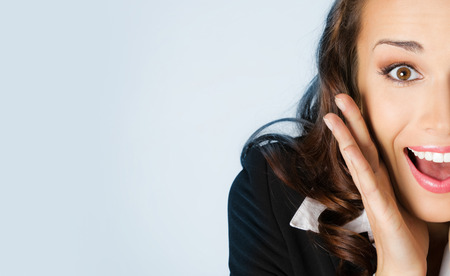 Portrait of young cheerful surprised businesswoman, against blue background photo