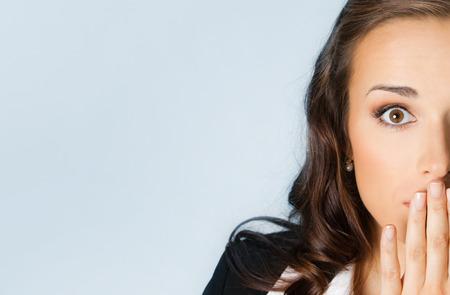 Überrascht excited junge Geschäftsfrau für mit Händen den Mund, vor blauem Hintergrund