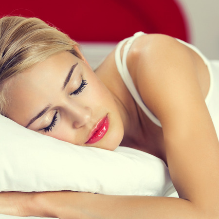 lazyness: Young blond woman sleeping on bed