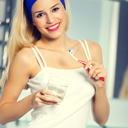 bathroom women: Portrait of young happy smiling blond woman bruhing teeth