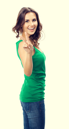 2 persons only: Cheerful smiling young woman showing two fingers or victory gesture, in smart green casual clothing
