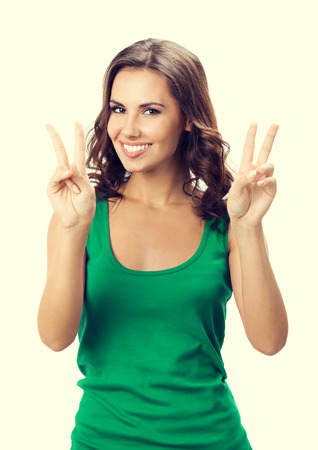 2 persons only: Cheerful young woman showing two fingers or victory gesture, in smart green casual clothing