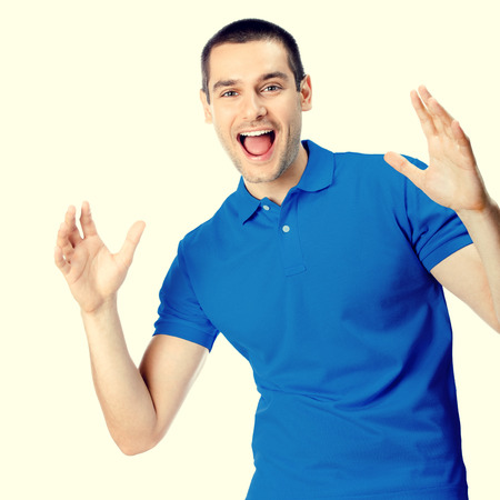 surprised man: Portrait of expressive happy surprised gesturing young handsome man in blue casual t-shirt clothing, looking at camera