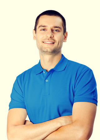 mani incrociate: Portrait of cheerful smiling young attractive handsome man in blue casual t-shirt clothing, with crossed arms, looking at camera