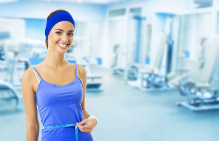 blank center: Woman in blue sports wear measuring waist with a tape measure, at fitness club or center, with blank copyspace area for slogan or text