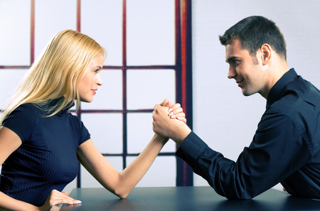 Young happy couple or two businesspeople fighting in arm wrestling, at office