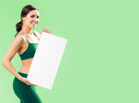 blank center: Portrait of smiling young woman in fitness wear showing blank signboard with copyspace area for text or slogan, over green background