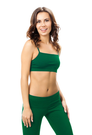 Full body portrait of smiling woman in green sports wear, isolated against white background