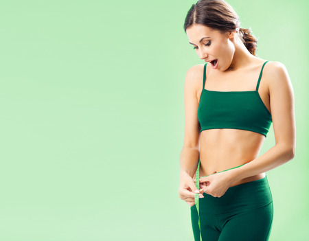 sportswear: Portrait of smiling young woman in fitness wear with tape, with blank copyspace area for text or slogan, over green background