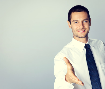 Portrait of smiling businessman giving hand for handshake, with blank copyspace area for text or slogan