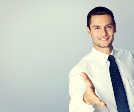 Retrato de hombre de negocios sonriente dando la mano para apretón de manos, con área de copyspace blanco para el texto o lema