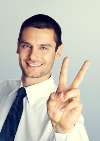 Cheerful smiling businessman showing two fingers, or victory gesture photo