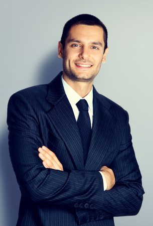 Portrait of smiling young businessman with crossed arms pose photo
