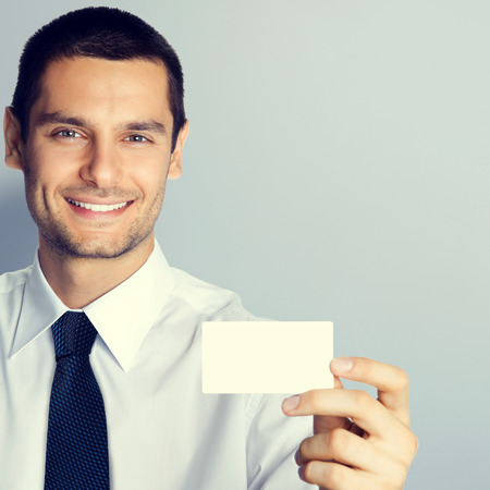 debet: Cheerful businessman showing blank business or plastic credit card, with copyspace area for text or slogan Stock Photo