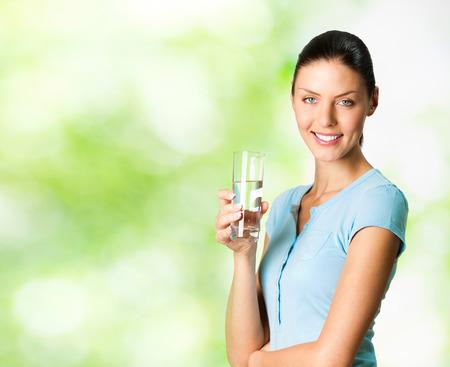 テキストまたはスローガンの空白 copyspace エリア、屋外、水のガラスと若い幸せな笑顔の女性