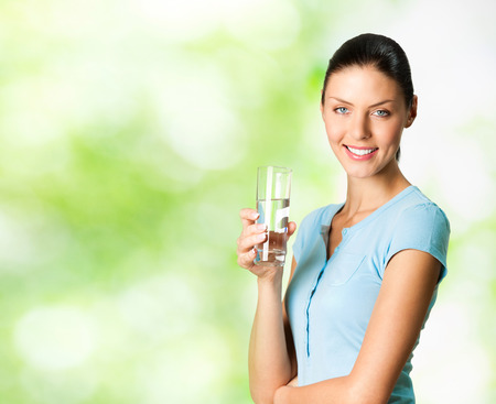 Young happy smiling woman with glass of water, outdoor, with blank copyspace area for text or slogan